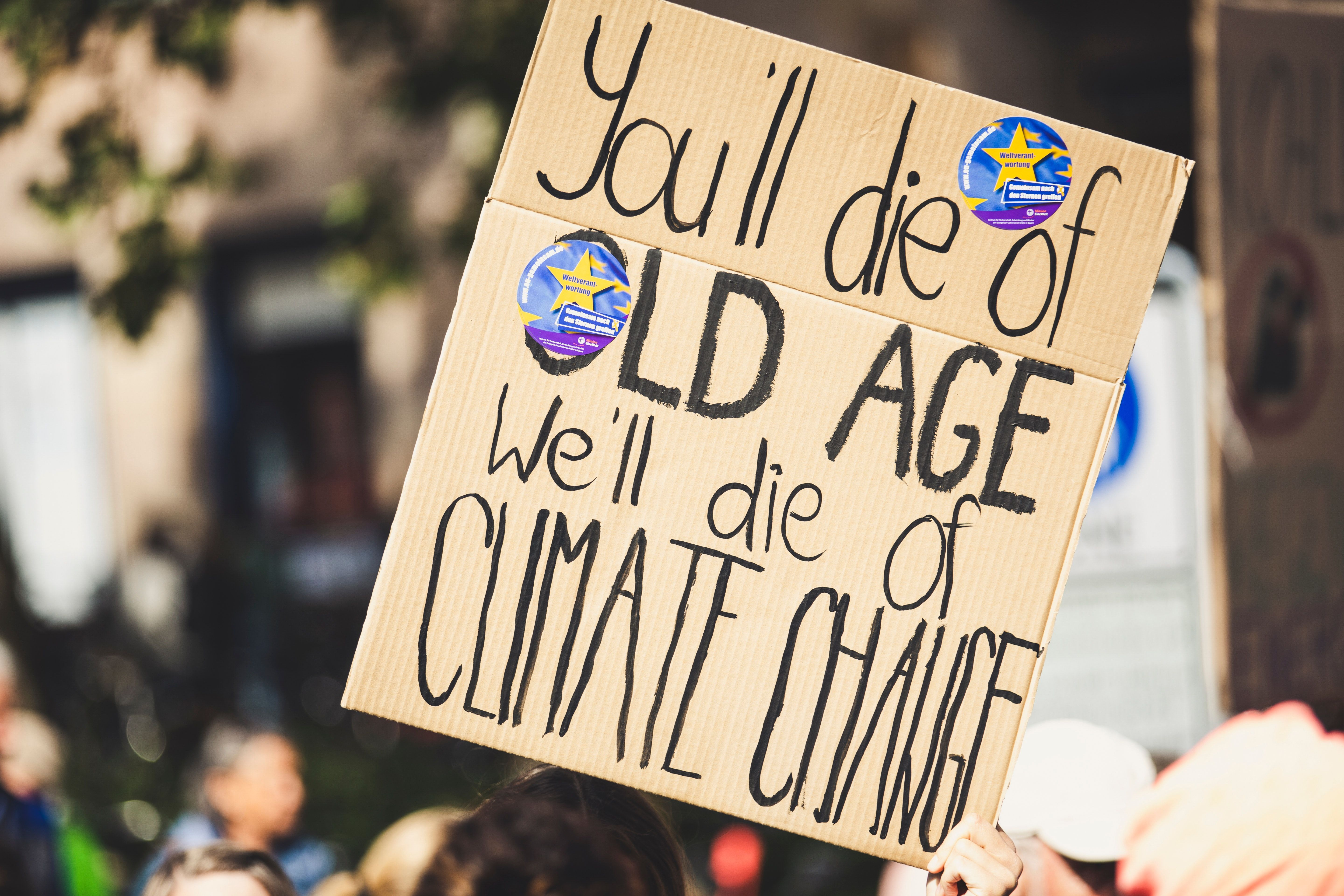 "A protest sign showing the words ""you'll die of old age, we'll die of climate change"""